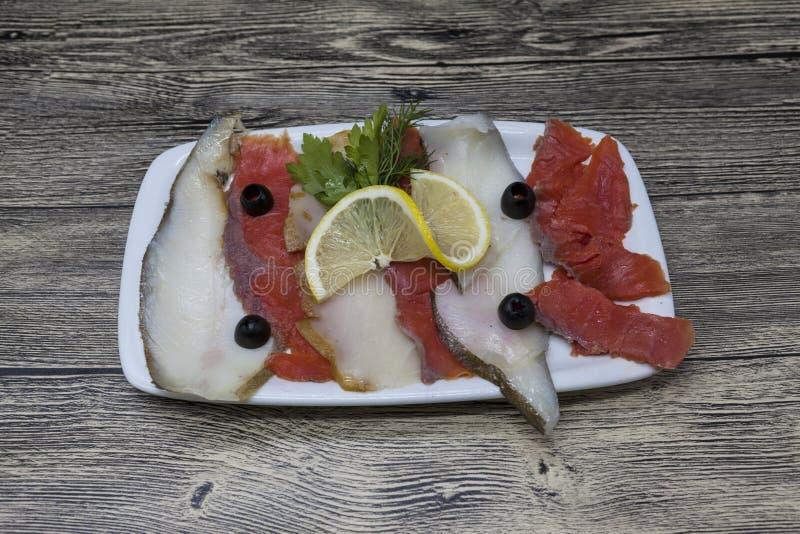 Uwędzeni rybi bakalie od Północnych morzy halibuty, łosoś Plasterki uwędzony łosoś i halibut na talerzu z plasterkiem cytryna obrazy royalty free