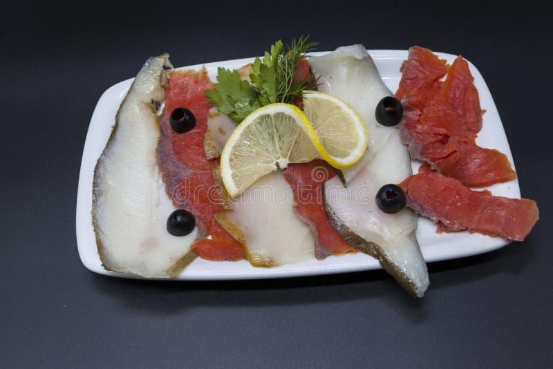 Uwędzeni rybi bakalie od Północnych morzy halibuty, łosoś Plasterki uwędzony łosoś i halibut na talerzu z plasterkiem cytryna obraz stock