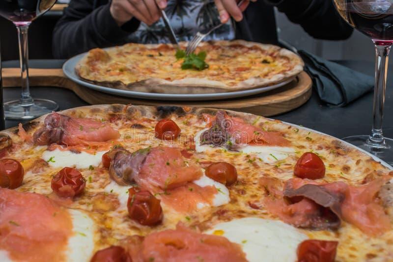 Uwędzona łososiowa pizza, czereśniowy pomidor i burrata ser z inną pizzą w plamie jako tło, typowy włoski jedzenie zdjęcie stock