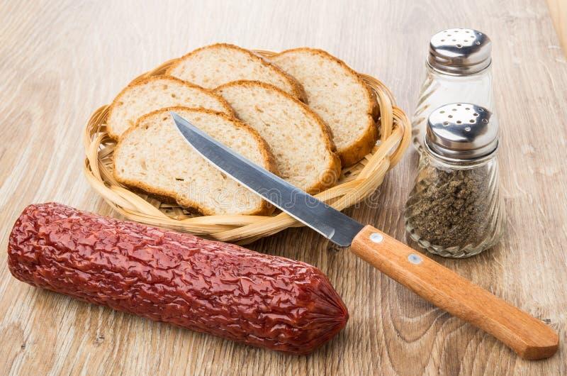 Uwędzona kiełbasa, chleb, sól, pieprz i nóż na stole, zdjęcie stock