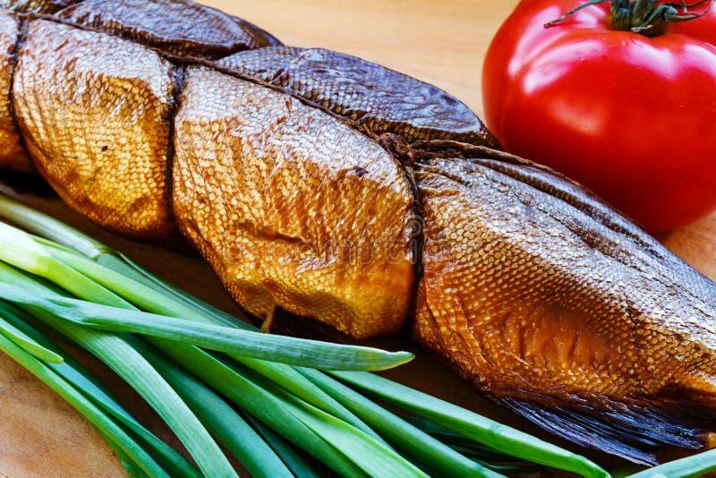 Uwędzona ryba na tnącej desce z pomidoru i zielonej cebuli zbliżeniem obrazy stock