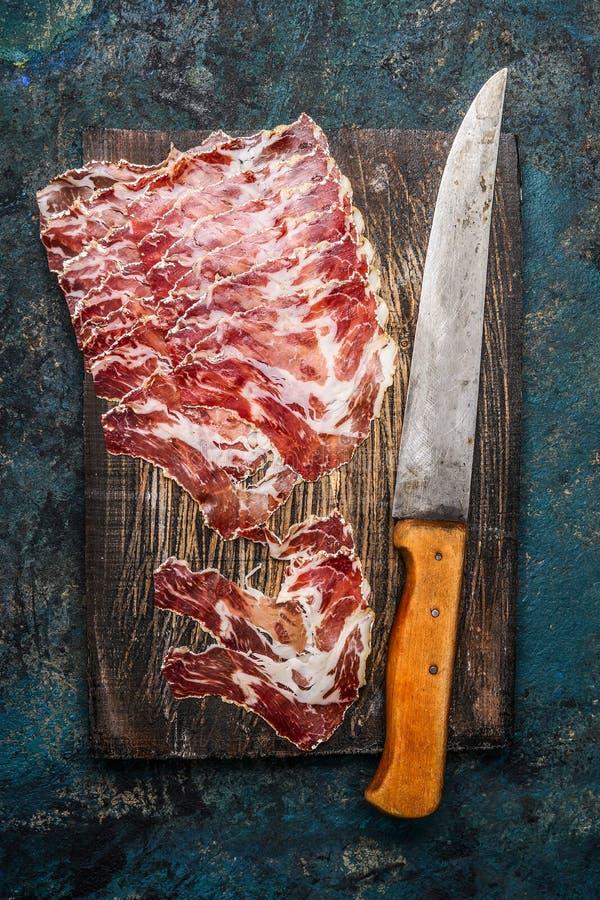 Uwędzony wieprzowiny mięso od coppa z kuchennym nożem na nieociosanym drewnianym tle Tradycyjna Włoska specjalność robić od wiepr zdjęcie stock