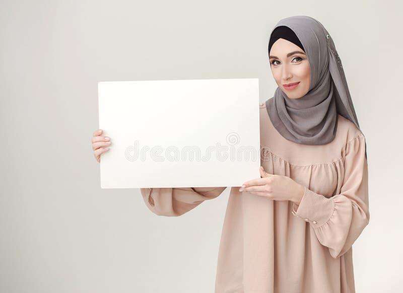 Uw aanbieding hier Vrouw in hijab die witte banner houden stock afbeelding
