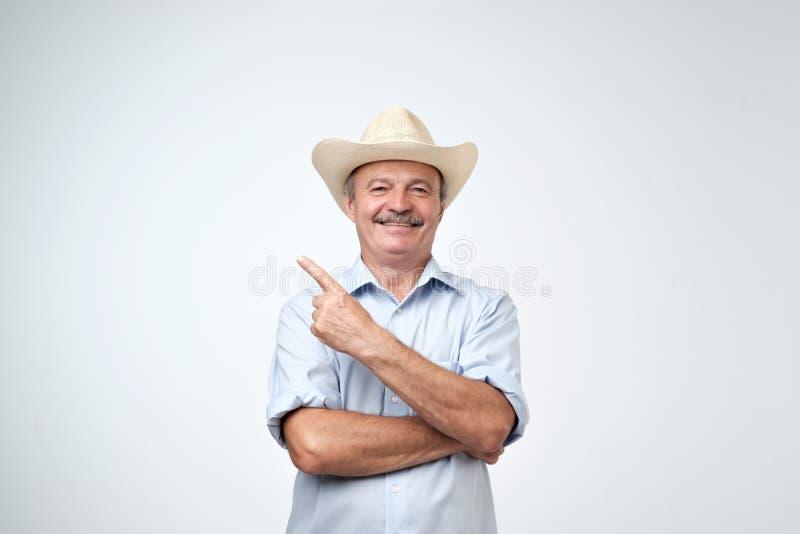 Uw hier reclame Studioportret van de knappe hogere mens in blauwe overhemd en cowboyhoed die exemplaarruimte tonen royalty-vrije stock foto