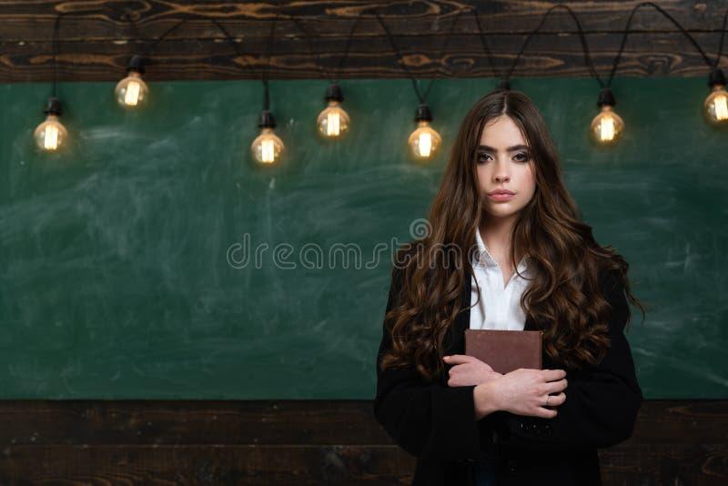 Uw tekst op Bord Klaar voor school Jonge leuke tiener in klaslokaal bij bord stock afbeelding
