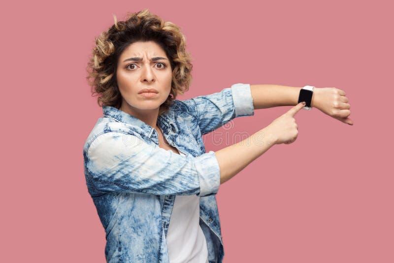 Uw Tijd loopt uit Portret van ernstige bazige jonge vrouw met krullend kapsel in toevallig blauw overhemd die en bevinden richten royalty-vrije stock foto's