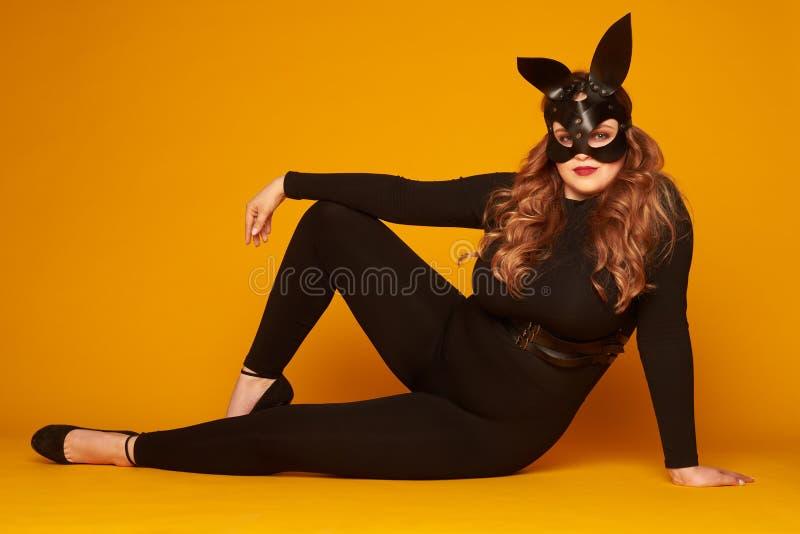 Uwodzicielska rozmiar dziewczyna w królika maskowy pozować na podłoga zdjęcie stock