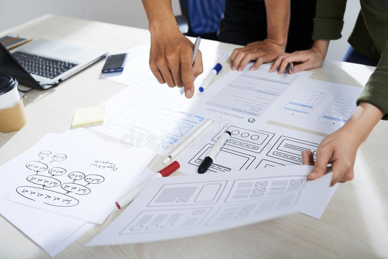 UX and UI designers discussing wireframes stock images