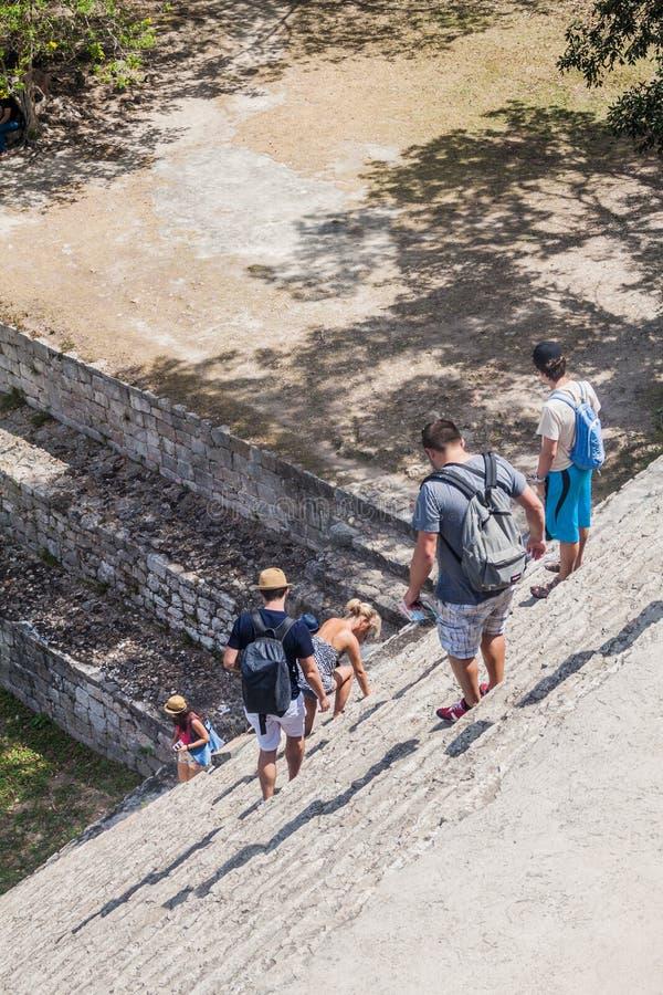 UXMAL, MÉXICO - 28 DE FEVEREIRO DE 2016: Os turistas descem da pirâmide grande nas ruínas da cidade maia antiga Uxmal, Mexi foto de stock royalty free
