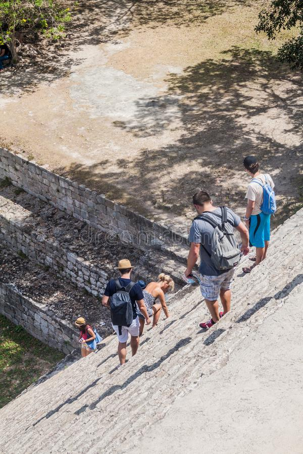 UXMAL, MEXICO - FEB 28, 2016: Tourists descend from the Grand Pyramid at the ruins of the ancient Mayan city Uxmal, Mexi royalty free stock photo