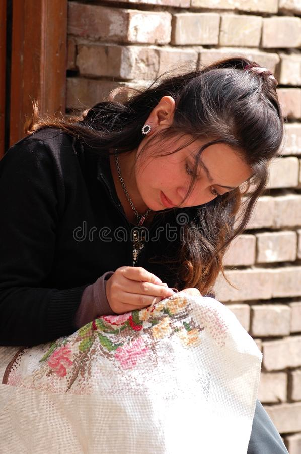 Uyghur girl embroidering royalty free stock photo