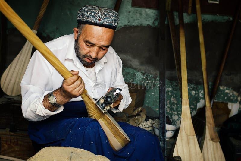 uyghur Mann, der ein Instrument herstellt, nannte dutar eine lokale Violinenversion stockfotografie