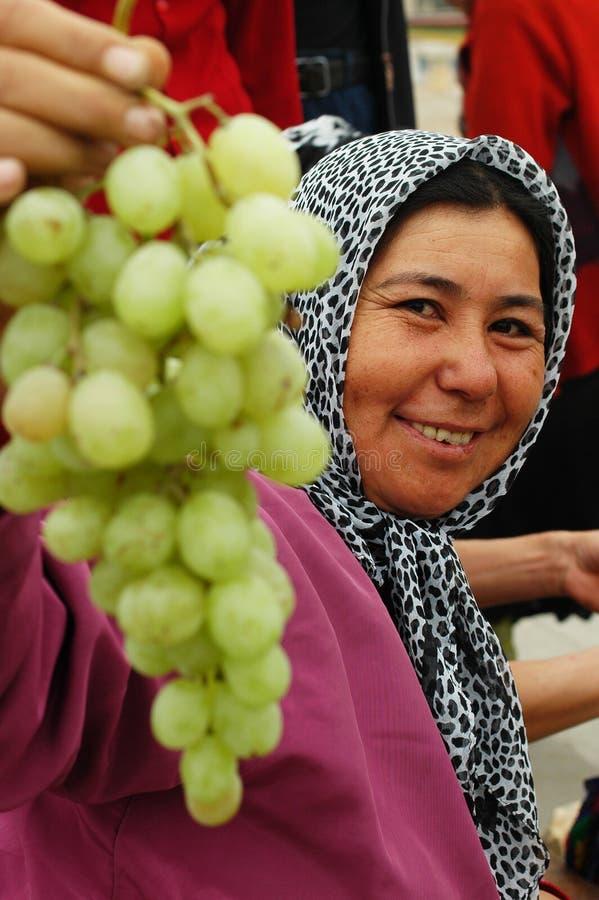 Uyghur woman selling grapes at market royalty free stock photos