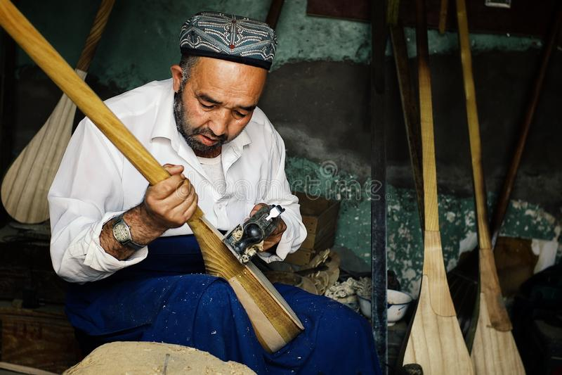 uyghurmannen som gör ett instrument, kallade dutar en lokal fiolversion arkivbild