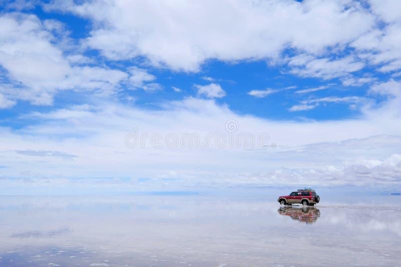 Uyuni,玻利维亚, 2018年1月31日:撒拉族de Uyuni盐湖舱内甲板被反射的表面上的路汽车, Uyuni,玻利维亚 免版税库存图片