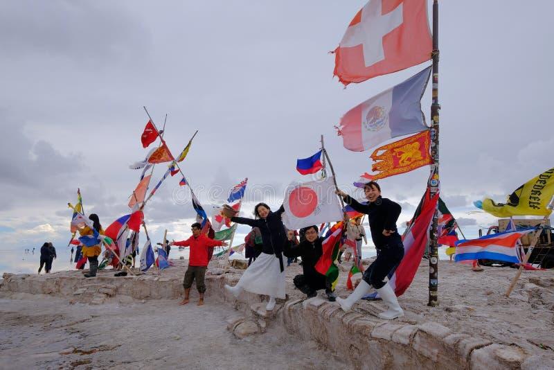 Uyuni,玻利维亚, 2018年1月31日:旗子纪念碑的游人在平的盐湖,大众观光业, Uyuni,玻利维亚 图库摄影