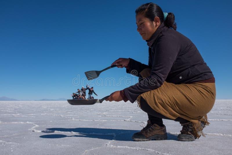 Uyuni, Bolivië, 11 Juni, 2015: Een groot bizar prospectief schot in Salar de Uyuni aangezien deze kok als zij kijkt heeft toerist royalty-vrije stock afbeeldingen