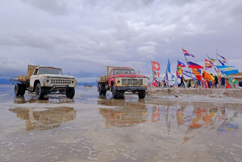 Uyuni, Bolivia, el 31 de enero de 2018: Camiones viejos en la superficie reflejada del plano del lago de sal de Salar de Uyuni, U fotos de archivo