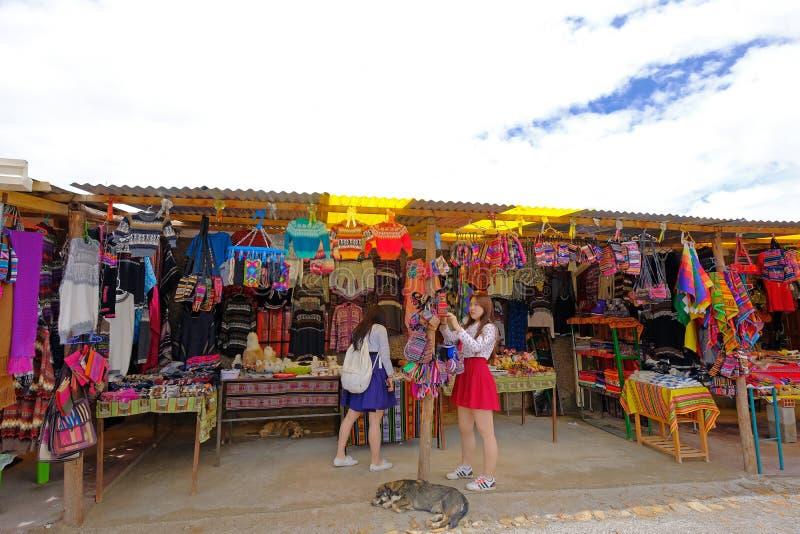UYUNI, BOLIVIA, EL 31 DE ENERO DE 2018: Dos turistas chinos que compran recuerdos cerca de la sal famosa plana, turismo total, Uy fotos de archivo