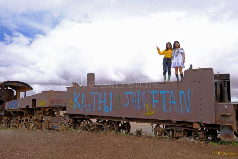 Uyuni, Bolivia, el 31 de enero de 2018: Dos turistas chinos que se colocan en un tren oxidado en el cementerio del tren, turismo  imagenes de archivo