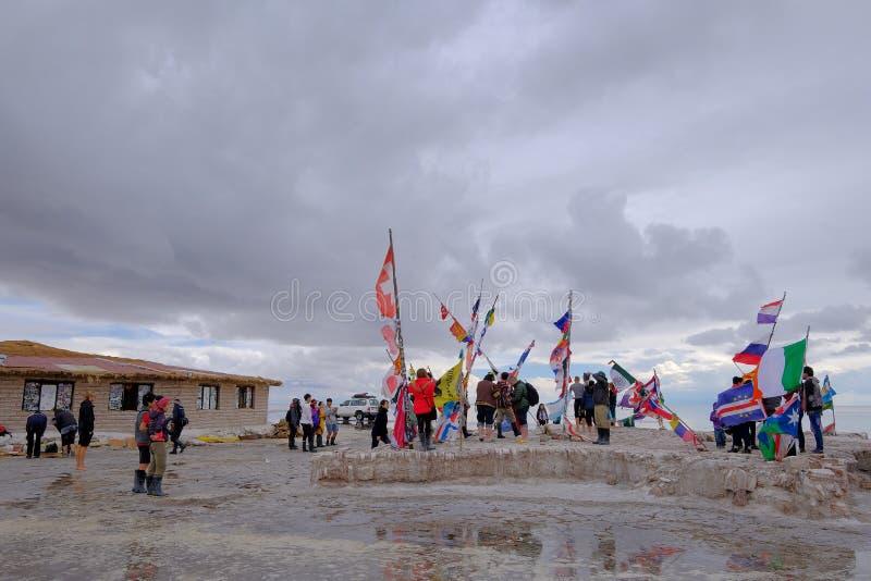 Uyuni, Bolivia, el 31 de enero de 2018: Turistas en el monumento de la bandera en el lago de sal plano, turismo total, Uyuni, Bol imágenes de archivo libres de regalías
