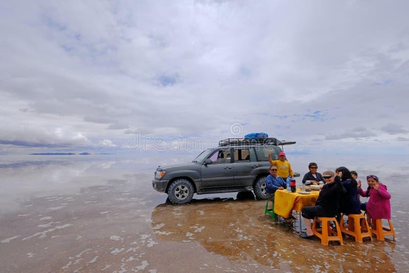 Uyuni, Bolivia, el 31 de enero de 2018: Turistas que almuerzan en el plano famoso del lago de sal de Uyuni, turismo total, Uyuni imagen de archivo libre de regalías
