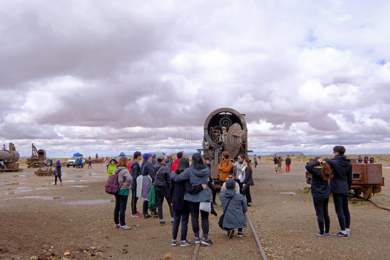 Uyuni, Bolivia, el 31 de enero de 2018: Turistas que se colocan en el cementerio del tren, turismo total, Uyuni, Bolivia fotografía de archivo
