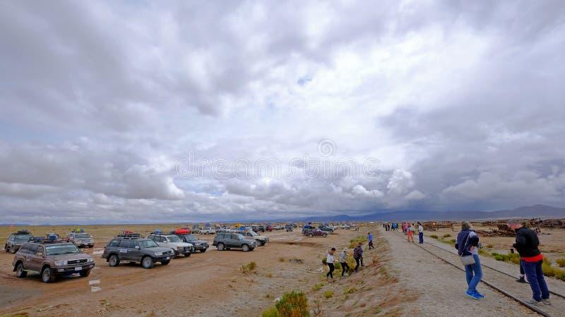 Uyuni, Bolivia, el 31 de enero de 2018: Turistas y coches del viaje en el cementerio del tren, turismo total, Uyuni, Bolivia fotos de archivo