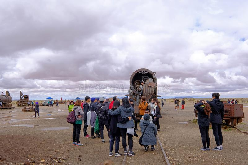 Uyuni, Bolivia, January 31, 2018: Tourists standing at the train graveyard, mass tourism, Uyuni, Bolivia stock photography