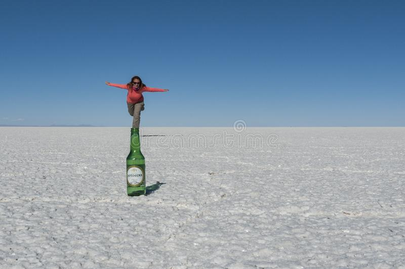 Tourist on the salt flat of Uyuni playing with the spatial perspective, creating a visual illusion. UYUNI SALT FLAT, BOLIVIA - August, 16 2017: Tourist on the stock images