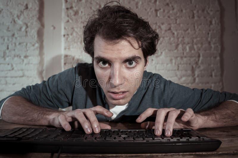 Uzale?niaj?cy si? interneta m?ody cz?owiek haczy? na komputerowym laptopie p??no przy noc? obraz stock