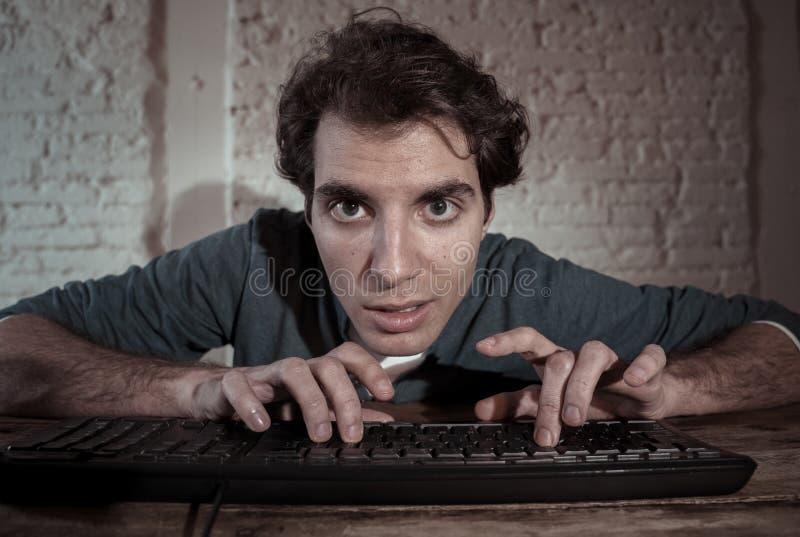 Uzale?niaj?cy si? interneta m?ody cz?owiek haczy? na komputerowym laptopie p??no przy noc? obrazy stock