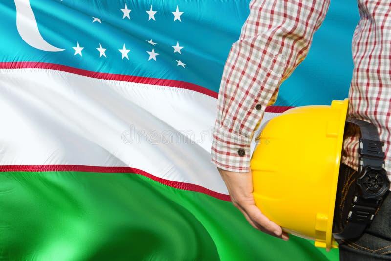 Uzbeka inżynier trzyma żółtego zbawczego hełm z machać Uzbekistan chorągwianego tło Budowy i budynku poj?cie obraz royalty free