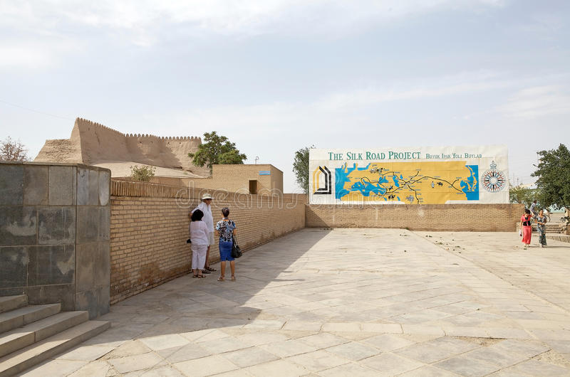 Uzbekistan. Tourists are looking the map of the Silk Road at the Itchan Kala, Khiva, Uzbekistan. Itchan Kala is the walled inner town of the city of Khiva. Since stock photography