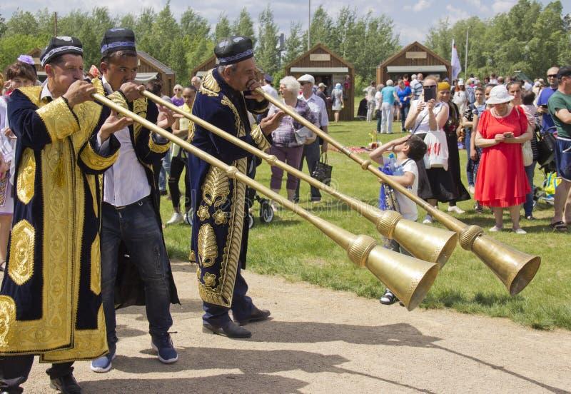 Uzbeks spelar länge mässingsmusikinstrument arkivbild
