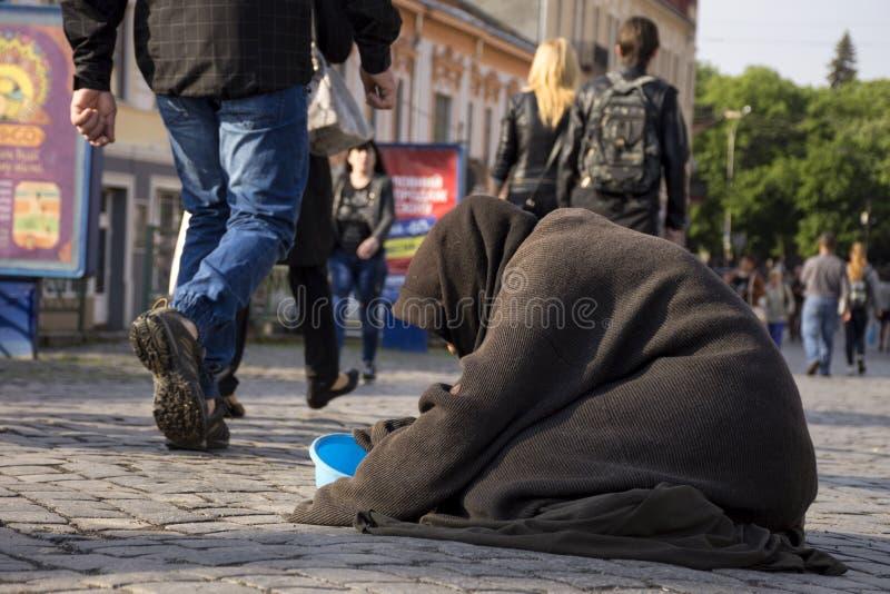 UZHGOROD, УКРАИНА - 3-ЬЕ МАЯ 2017: Плохая старуха умоляя для милостынь стоковые изображения