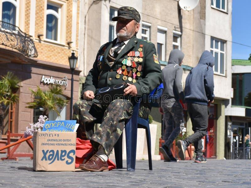 UZHGOROD, UCRÂNIA - 9 DE MAIO DE 2017: Veterano de guerra que implora o dinheiro pela SU foto de stock