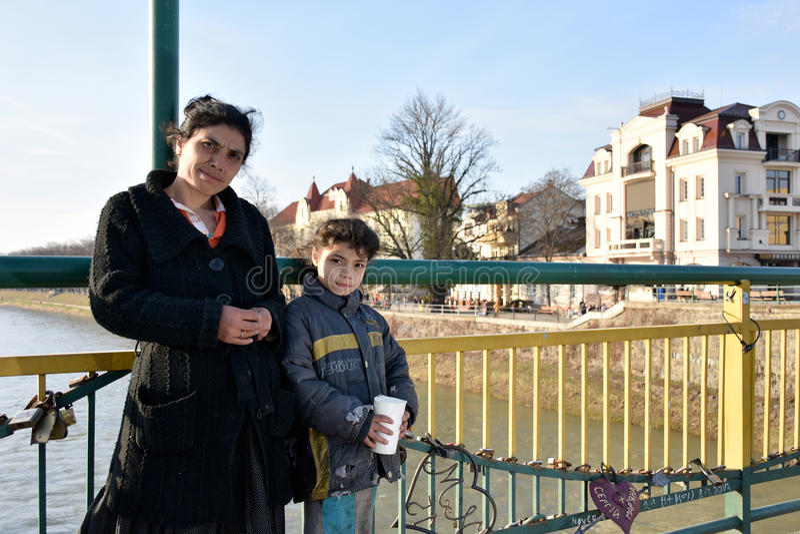 UZHGOROD UKRAINA - MARS 04, 2017: Fattig kvinna med liten flicka b arkivbilder