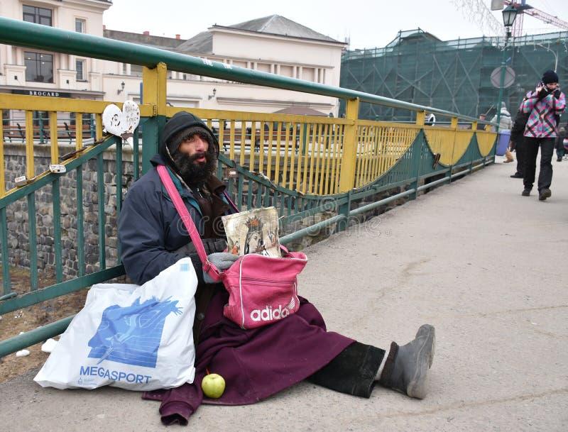 UZHGOROD,UKRAINE - FEBRUARY 16, 2017: Poor man begging for alms. In the street of Uzhhorod, Ukraine. Beggar sitting on the ground stock photos