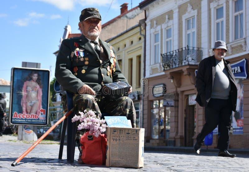 UZHGOROD,UKRAINE -MAY 09, 2017: War veteran begging money for surgery of his wife in Uzhgorod, Ukraine. stock photography