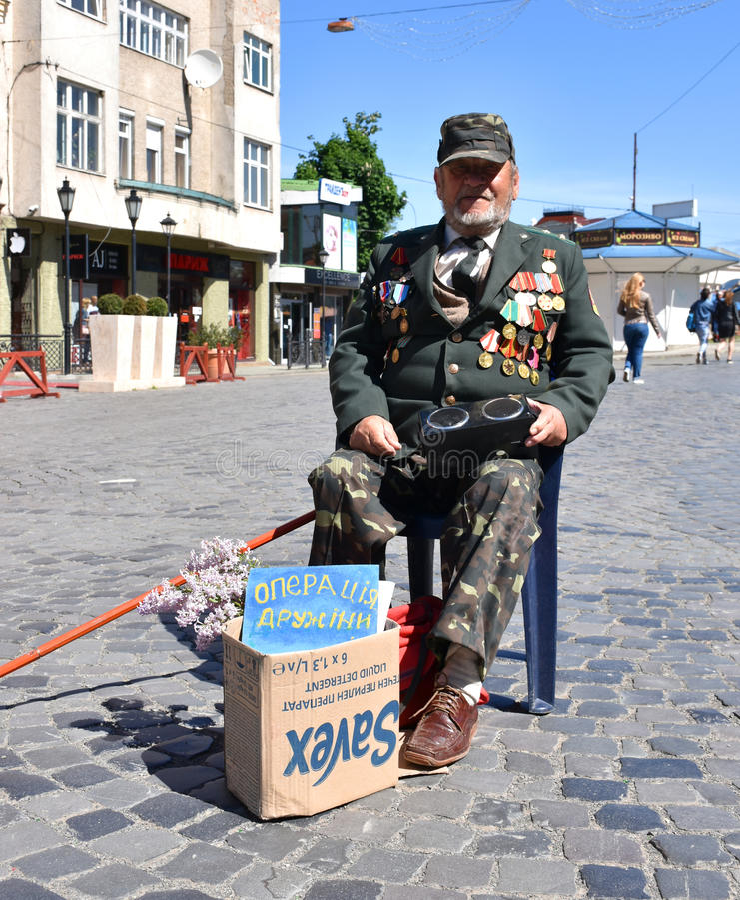 UZHGOROD,UKRAINE -MAY 09, 2017: War veteran begging money for surgery of his wife in Uzhgorod, Ukraine. royalty free stock photos