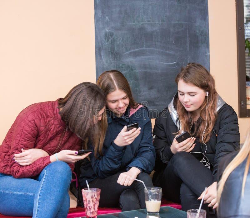 """UZHHGOROD, DE OEKRAÏNE € """"16 APRIL, 2019: Groep meisjes die celtelefoon bekijken in het stadsterras in Uzhhorod stock fotografie"""