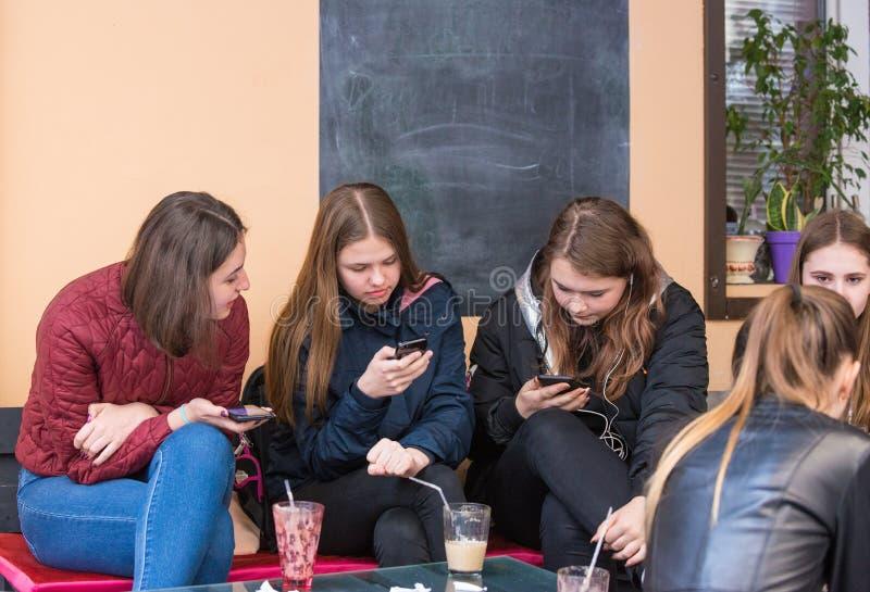 """UZHHGOROD, DE OEKRAÏNE € """"16 APRIL, 2019: Groep meisjes die celtelefoon bekijken in het stadsterras in Uzhhorod royalty-vrije stock afbeelding"""
