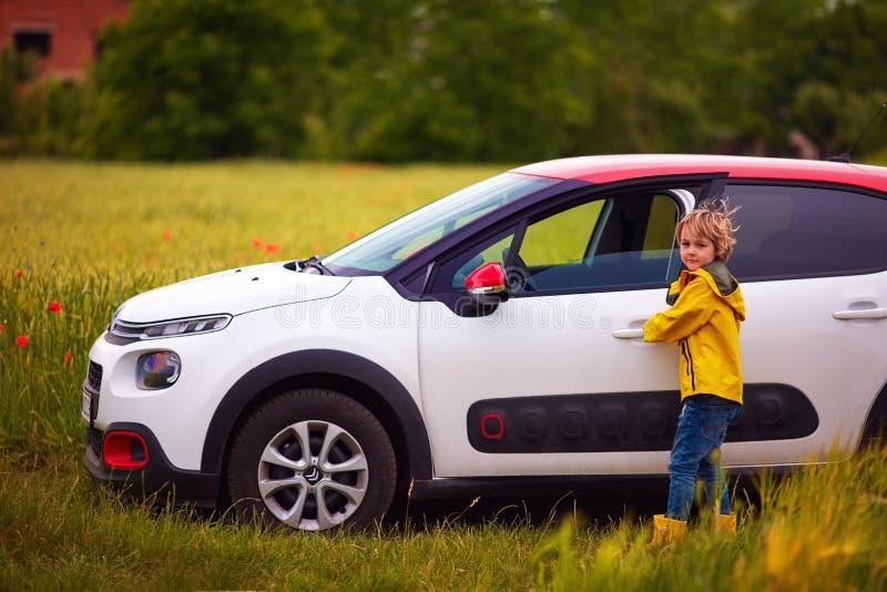 UZHHOROD, DE OEKRAÏNE - MEI 25, 2018: Het jonge geitje, jongen opent de deur van de auto van Citroën C3, bij het papavergebied royalty-vrije stock afbeeldingen