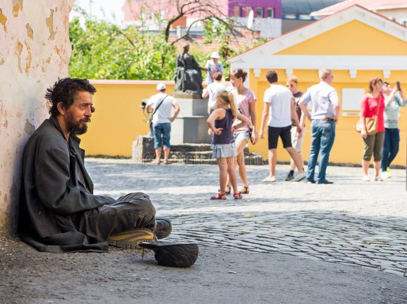 UZHHOROD, UKRAINE - AUGUST 21, 2016: Poor man begging for alms. Near the church in Uzhhorod, Ukraine royalty free stock image
