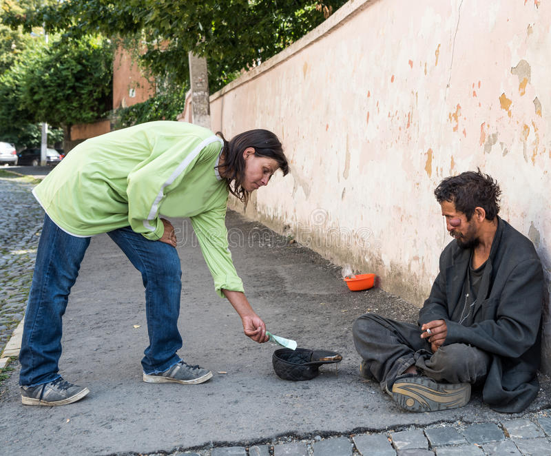 UZHHOROD, UKRAINE - AUGUST 21, 2016: Poor man begging for alms. Near the church in Uzhhorod, Ukraine stock photo