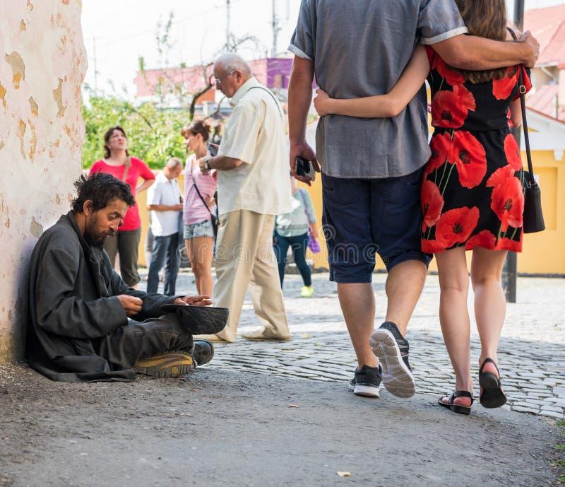 UZHHOROD, UKRAINE - AUGUST 21, 2016: Poor man begging for alms. Near the church in Uzhhorod, Ukraine royalty free stock images