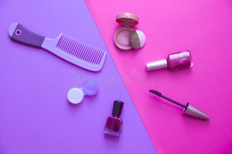 Uzupełnia kosmetyki na purpurach i różowi tło zdjęcia stock
