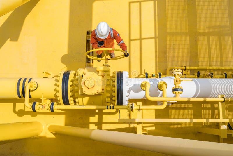 Válvula abierta del operador de la producción para permitir el gas que fluye a la línea tubo de mar para los gases y el petróleo  fotografía de archivo