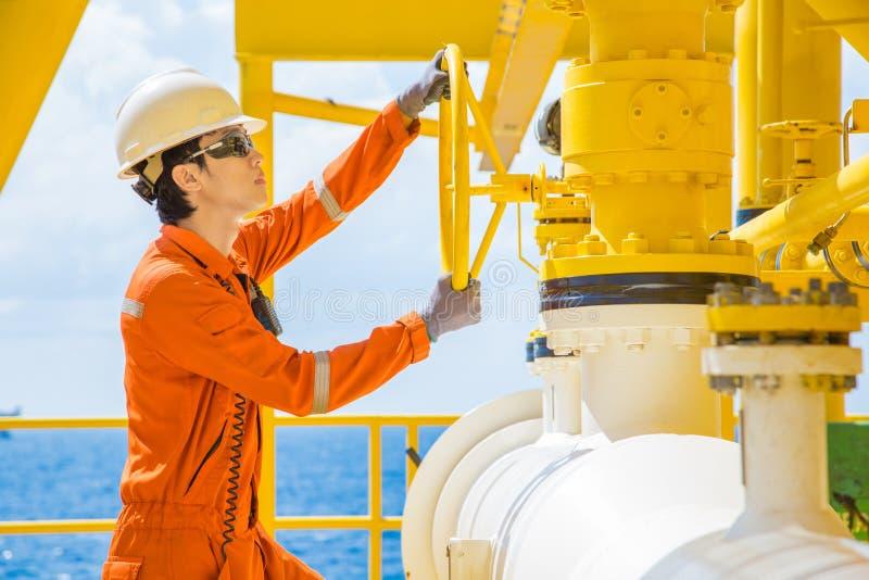 Válvula abierta del operador de la producción para permitir el gas que fluye a la línea tubo de mar para el gas y el petróleo cru fotografía de archivo
